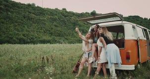 Retro skåpbil i mitt av naturen, grupp av härliga damer som tar selfies som sitter på baksidan av skåpbilen som är lycklig lager videofilmer
