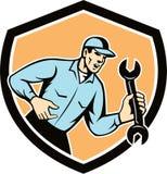Retro sköld för mekanikerShouting Holding Spanner skiftnyckel Arkivfoto