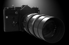 Retro SLR Camera in b&w. On black background with lights coming from behind Royalty Free Stock Photos