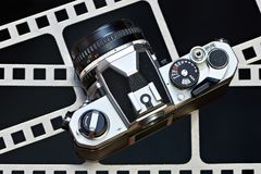 Retro SLR camera on background of perforation film. Retro SLR camera on the background of the perforation of film Stock Photography