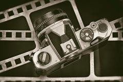 Retro SLR camera on background of perforation film. Retro SLR camera on the background of the perforation of film Royalty Free Stock Photo