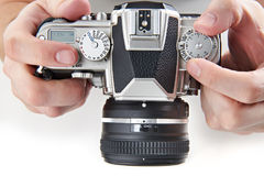 Retro SLR camera in hands of photographer. Retro SLR camera in the hands of the photographer closeup Stock Photography