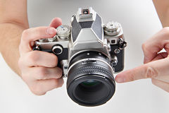 Retro SLR camera in hands of photographer. Retro SLR camera in the hands of the photographer isolated closeup Royalty Free Stock Image
