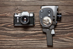 Retro SLR camera and mechanical movie camera on wooden backgroun Royalty Free Stock Images