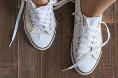 Retro sneakers left on wooden floor Royalty Free Stock Photography