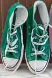 Retro sneakers left on wooden floor Stock Photos
