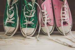 Retro sneakers left on wooden floor Stock Photo