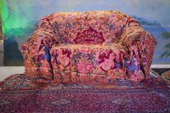 Retro sofa with decorative coverlet in the room with wallpaper palms in the evening for a holiday stock photo