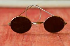 Retro- Sonnenbrille auf braunem hölzernem Hintergrund Lizenzfreie Stockbilder