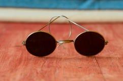 Retro- Sonnenbrille auf braunem hölzernem Hintergrund Lizenzfreie Stockfotografie