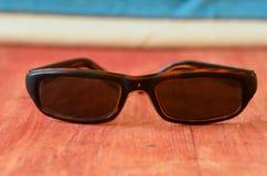 Retro- Sonnenbrille auf braunem hölzernem Hintergrund Stockbilder