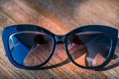 Retro- Sonnenbrille auf Holztisch lizenzfreie stockfotografie