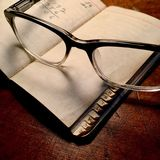 Retro spectacles with little black book. Stock Photos