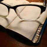 Retro spectacles with little black book. Royalty Free Stock Photos