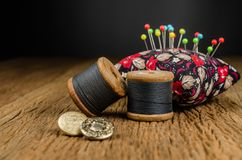 retro spool thread with pincushion on wooden board Royalty Free Stock Image