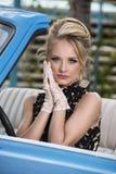 Retro stående av den ursnygga blondinen i en blå bil Royaltyfria Bilder