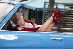 Retro stående av en härlig blondin i bilen Royaltyfria Bilder
