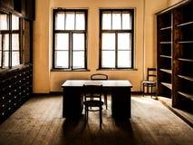 Retro stanza dell'ufficio di stile con la tavola di legno, le vecchie sedie ed i gabinetti Tema d'annata immagini stock