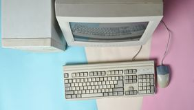 Retro stationary computer on colored background. Monitor, system unit, computer mouse. Obsolete Technologies, top view. Retro stationary computer on colored stock images