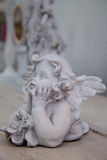 Retro statuette of an angel on a wooden table. Royalty Free Stock Photography