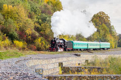 Retro steam train approaches mountains Royalty Free Stock Photo