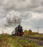 Retro steam train approaches mountains Royalty Free Stock Images