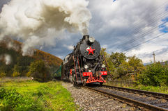 Retro steam train approaches mountains Royalty Free Stock Photography