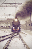 Retro steam train departs from the railway station at sunset. Stock Photo