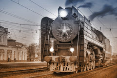 Retro Steam Train Stands On The Station At Evening Time. Stock Photos