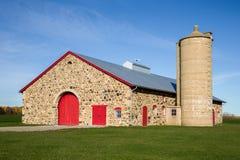 Retro stenladugård med ljusa röda dörrar Arkivbilder