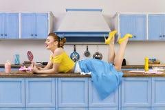 Retro- Stift herauf die Lügenentspannung der Mädchenfrau auf Küche stockfotografie