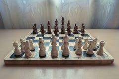 Retro stijl houten materiële schaakbord met schaakstukken plaatste voor strategisch meningsspel klaar stock foto's