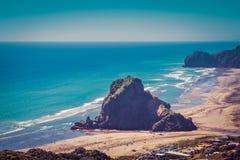 Retro-stijlfoto van Lion Rock in het centrum van Piha-strand op een mooie de zomerdag Auckland, Nieuw Zeeland royalty-vrije stock afbeelding