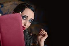 Retro stijlvrouw met menuboek dat (uit eruit ziet) Royalty-vrije Stock Fotografie