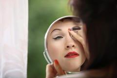 Retro stil för flicka som applicerar sminket som inomhus ser spegeln royaltyfria bilder