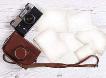 Retro still camera. And some old photos on wooden table background stock photography