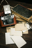 Retro still camera and some old photos on wooden table background.  stock photography