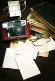 Retro still camera and some old photos on wooden table background Stock Images