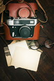 Retro still camera and some old photos. On wooden table background royalty free stock photography