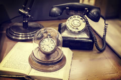 Retro still life. Still life with retro telephone and table clock Stock Images