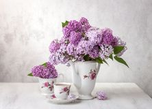 Retro still life with bouquet of Lilac and cup of tee Royalty Free Stock Photo