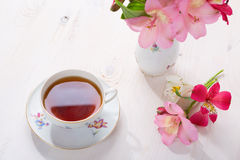 Retro still life with cup of tea and flowers Stock Photo