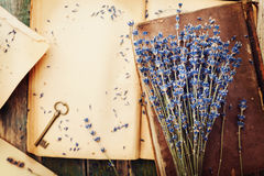 Retro still life with vintage books, key and lavender flowers, nostalgic composition on wooden table top view. Stock Photos