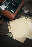 Retro stilla kamera och några gamla foto på trätabellbakgrund Arkivbild