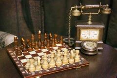 Retro stilleben för tappning med visartavlatelefonen och schack Arkivfoto