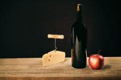 Retro stilleven met wijn en kaaskurketrekker stock afbeeldingen