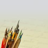 Retro stilreservoarpennasamling Åldriga färgrika pennor, gul vitbokbakgrund för lutning Konstnärtillbehör Royaltyfri Foto