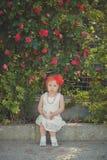Retro- stilvolles gekleidetes blondes junges Babykind, aufwerfend in Central- Parkgarten, den couturer weißes Kleidroten Bandana  Stockfoto