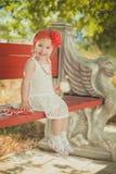 Retro- stilvolles gekleidetes blondes junges Babykind, aufwerfend in Central- Parkgarten, den couturer weißes Kleidroten Bandana  Lizenzfreie Stockbilder