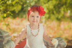 Retro- stilvolles gekleidetes blondes junges Babykind, aufwerfend in Central- Parkgarten, den couturer weißes Kleidroten Bandana  Stockfotos